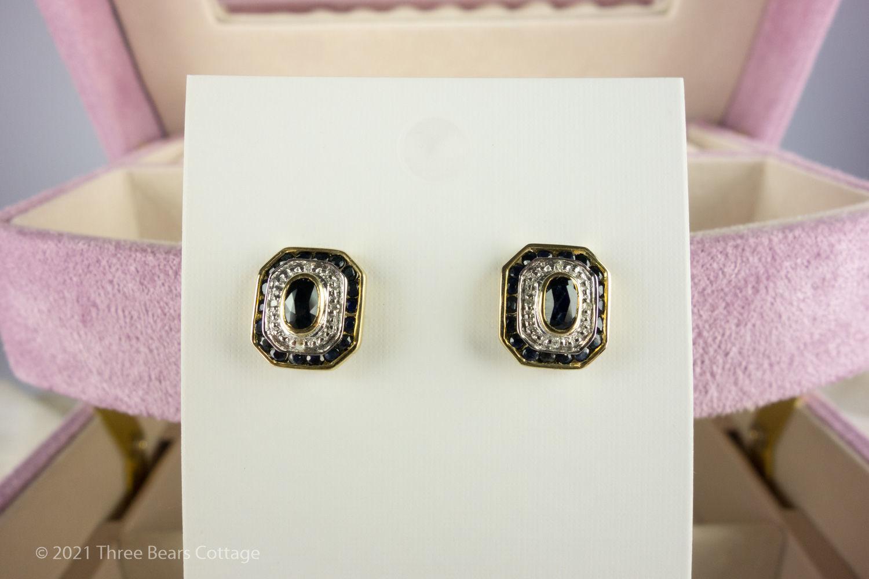 Rectangular sapphire and diamond stud earrings against white card